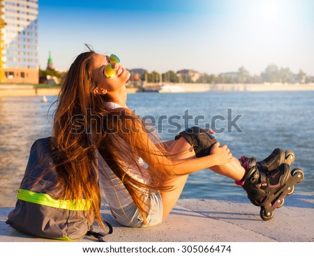 Beautiful sensuality elegance brunette woman, has happy fun cheerful smiling face, white shirt, blue jeans shorts. Has slim sport tan body. Motion on great rollerblading urban city. Portrait nature.  - stock photo