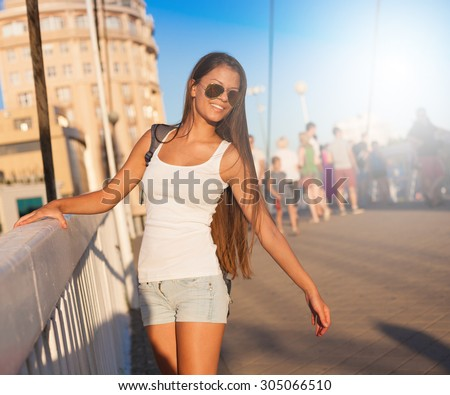 Beautiful sensuality elegance brunette woman, has happy fun cheerful smiling face, white t-shirt, blue jeans shorts, slim sport tan body. Portrait nature urban city. Sunny megalopolis
