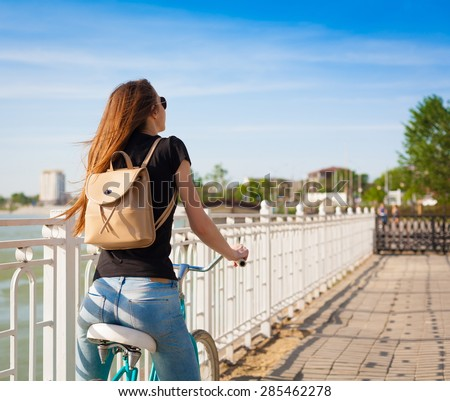 beautiful sensuality elegance haired hair back woman happy fun blue sky black t-shirt jeans bicycle urban city portrait nature slim sport body hobby equipment riding bike cyclist ass - stock photo