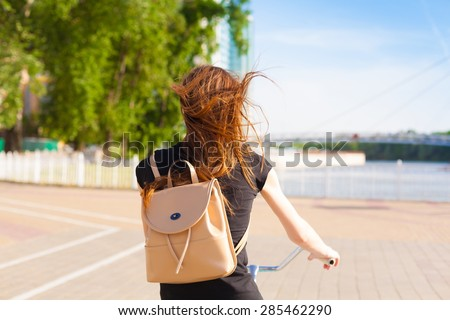 beautiful sensuality elegance haired hair back woman happy fun blue sky black t-shirt jeans bicycle urban city portrait nature slim sport body hobby equipment riding bike cyclist  - stock photo