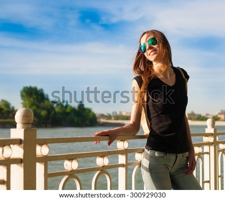 Beautiful sensuality elegance haired hair woman, has happy fun cheerful smiling face, black shirt, blue jeans. Has slim sport body. Portrait nature urban city.  - stock photo