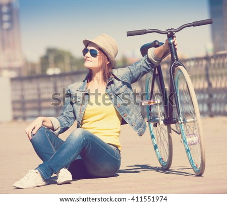 Beautiful sensuality elegance haired woman cyclist, has happy fun cheerful smiling face, yellow t-shirt, blue jeans and hat, sport body. Motion on great bicycle in urban city. Portrait nature.  - stock photo
