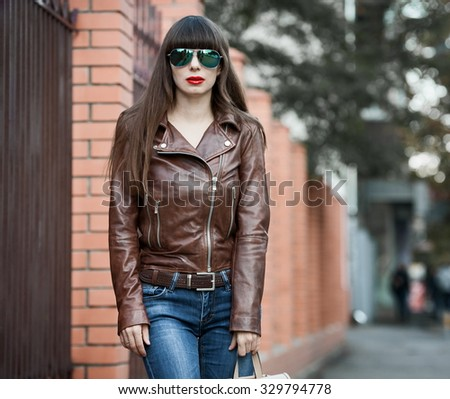 Beautiful sensuality elegance haired woman, has happy fun cheerful smiling face, brown leather jacket, blue jeans and sunglasses, sexy lips. Pure makeup.  - stock photo