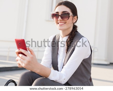 beautiful sensuality elegance lady brunette woman happy face with gray business suit white blouse, urban city professional portrait, nature lifestyle, background slim body, sunglasses red smart phone - stock photo