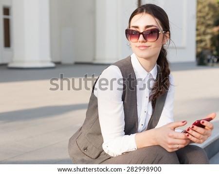 beautiful sensuality elegance lady brunette woman happy face with gray business suit white blouse, urban city professional portrait, nature lifestyle, background slim body, sunglasses leather handbag - stock photo