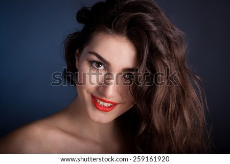 beautiful sensuality elegance lady smiling joy fun woman face with brown eyes, studio portrait and professional nature romantic wellness pure  gloss  hair brunette white teeth red lips blue background - stock photo
