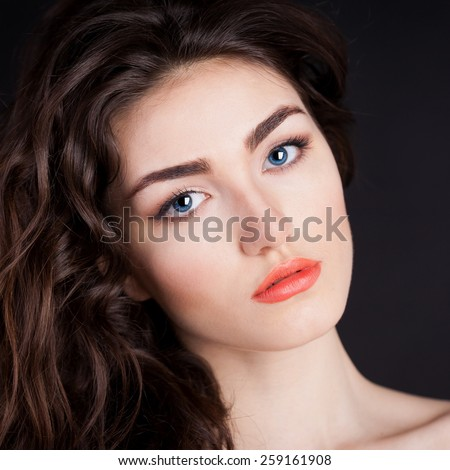 beautiful sensuality elegance lady woman serious face with blue contact lenses, studio portrait and professional light, nature romantic wellness pure makeup, gloss  hair brunette, black background - stock photo