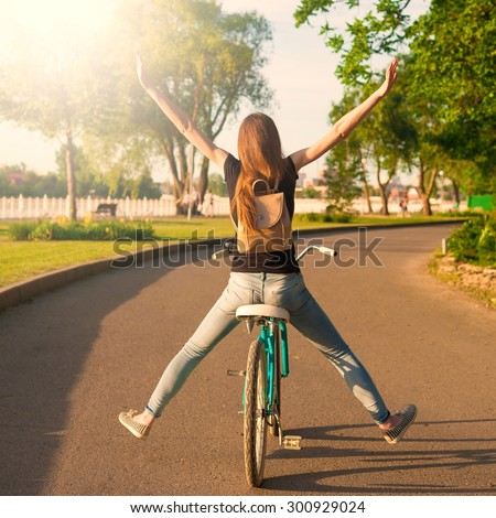 Beautiful sensuality elegance red hair back woman cyclist, has black shirt, blue jeans. Has slim sport body and ass. Motion on great bicycle in urban city. Portrait nature amazing sunset.  - stock photo