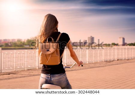 Beautiful sensuality elegance red hair back woman cyclist, has black shirt, blue jeans. Has slim sport body and ass. Motion on great bicycle in urban city. Portrait nature amazing sunset. teenager - stock photo