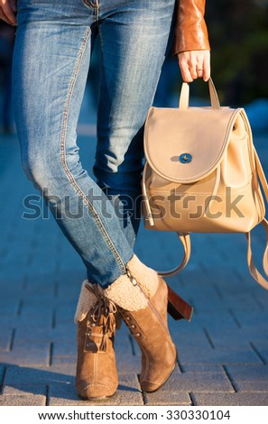 Beautiful sensuality elegance slim woman legs, dressed in leather suede beige boots and blue jeans, holding handbag backpack. - stock photo