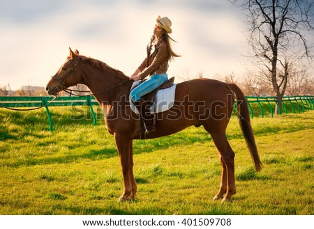 Beautiful sensuality elegance woman cowgirl, riding a horse. Clothed blue jeans, brown leather jacket and hat. Has slim sport body. Portrait nature. People and animals. Equestrian.