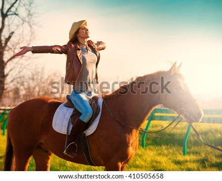 Beautiful sensuality elegance woman cowgirl, riding a horse. Clothed blue jeans, brown leather jacket and hat. Has slim sport body. Portrait nature. People and animals. Equestrian. Amazing sunset - stock photo
