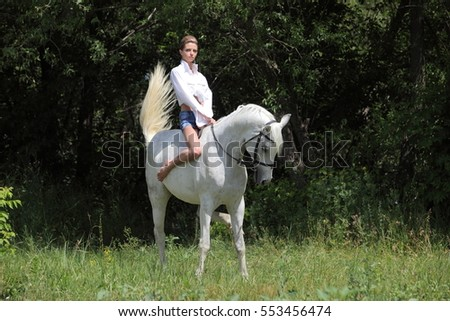 Beautiful sensuality elegance woman cowgirl, riding a white arabian horse