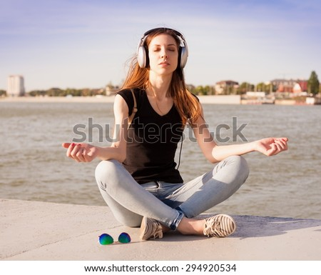 beautiful sensuality haired hair woman happy fun cheerful look smiling blue sunglasses black t-shirt jeans river urban city portrait nature slim body bright rest meditation yoga music headphones - stock photo