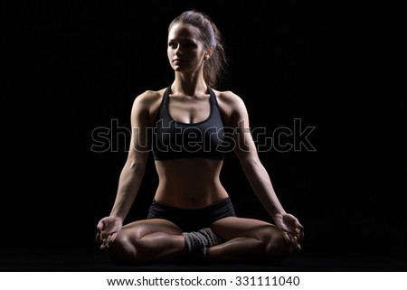 Beautiful serene cool young fit woman in sportswear practicing yoga, sitting in Sukhasana, Easy Posture, asana for meditation, pranayama, full length, front view, studio image, black background - stock photo