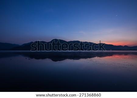 Beautiful serene lake and mountain  with morning twilight sky. - stock photo