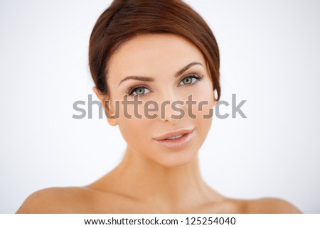 Beautiful serene woman with lovely smooth skin and a gentle look posing against a white background with bare shoulders