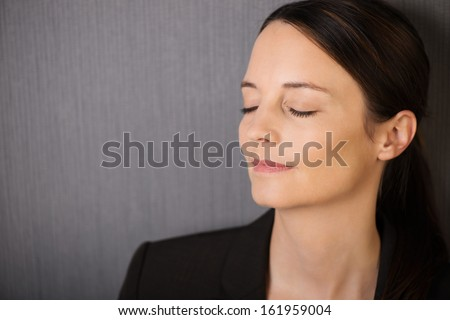 Beautiful serene young woman with her eyes closed in meditation standing against a grey background with copyspace - stock photo