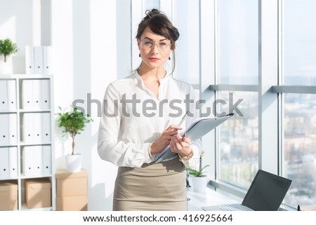 Beautiful, serious consultant wearing glasses and a formal office suit, holding her work stationary, looking at camera. - stock photo