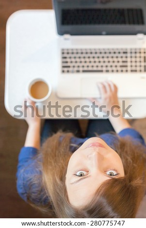 Beautiful serious woman looking at the camera and uses laptop at home or at office, working remotely at white table. Computer connected to the Internet via Wi fi. Top view