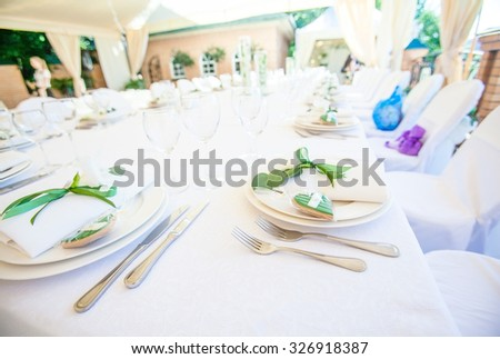 Beautiful serving at banquets, white plate, white tablecloth green ribbon to decorate