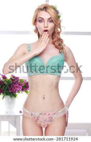 Beautiful sexual blonde in a lingerie on a background a window - stock photo