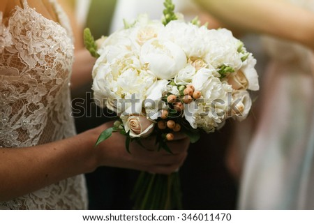Beautiful sexual bride in elegant dress holding white wedding bouquet - stock photo