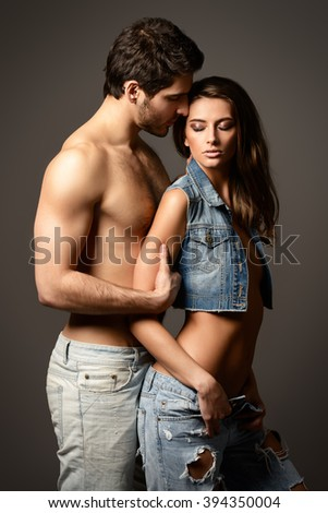 Beautiful sexual couple topless playing in love games. Jeans style. Studio shot. - stock photo