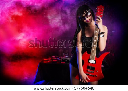 Beautiful sexual girl playing electric guitar in the old garage.  - stock photo