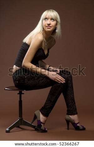 Beautiful sexual girl sits on chair on brown background