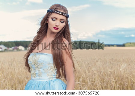 beautiful sexualintelligance girl model in blue dress with pink lips design demonstrates a rim on the head in a field on a Sunny day