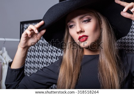 beautiful sexy attractive girl in a black hat with red lipstick in fashion photography in a black dress with a bright evening make-up - stock photo
