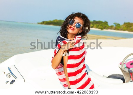 Beautiful sexy awesome hipster girl, brunette on the beach, near the high-speed boat, wrapped in a cloth with the image of the American flag, wet hair, tanned healthy skin, sunglasses, lifestyle - stock photo