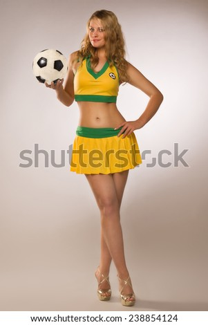 beautiful sexy blond cheerleader whit soccer ball on a gray studio background - stock photo