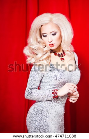 Beautiful Sexy Blond Girl. Long Hair. Blonde isolated on red Background. Holiday Makeup.Make-up. Glamour Woman