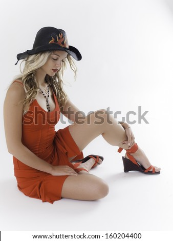 Beautiful sexy blond model girl in red dress with flames cowboy hat - stock photo
