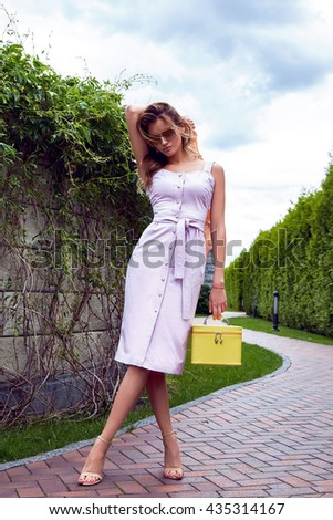 Beautiful sexy blond woman makeup wear stylish short dress for party and walk glamour fashion clothes silk shawl accessory bag and sunglasses good summer weather park outdoor gate green trees street