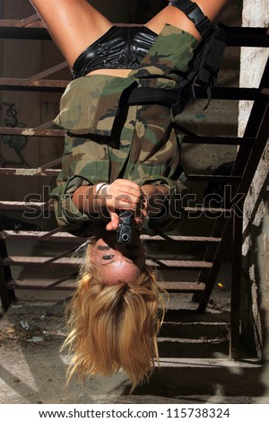 Beautiful sexy blond woman with gun hanging upside down - stock photo