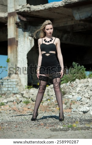 Beautiful sexy blonde girl in a black dress and stockings posing on a background of ruins