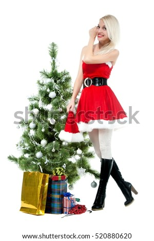 Beautiful sexy blonde girl in a Christmas costume at a Christmas tree on a white background isolated