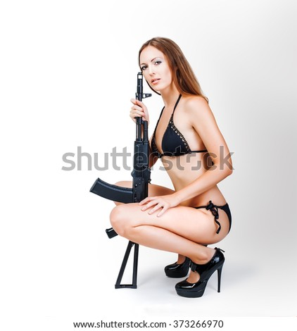 Beautiful sexy blonde girl in bikini holding airsoft rifle sitting in studio on white background