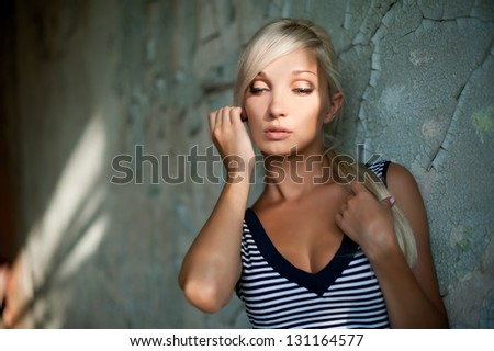 Beautiful sexy blonde girl posing in an old building collapsed