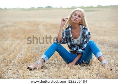 Beautiful sexy blonde girl posing on sloping field