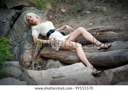 Beautiful sexy blonde girl posing on the felled trees