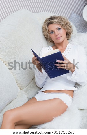 beautiful sexy blonde girl reading a book lying on sofa