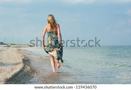 Beautiful sexy blonde girl running on the beach - stock photo