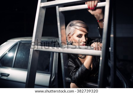 beautiful sexy blonde girl staying in garage near disassembled vintage car and ladder; attractive woman with short haircut staying near old bmw; - stock photo