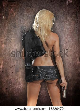 Beautiful sexy blonde girl with gun - stock photo