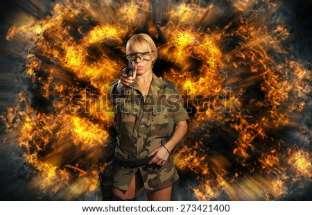 Beautiful sexy blonde girl with gun over exploding background - stock photo