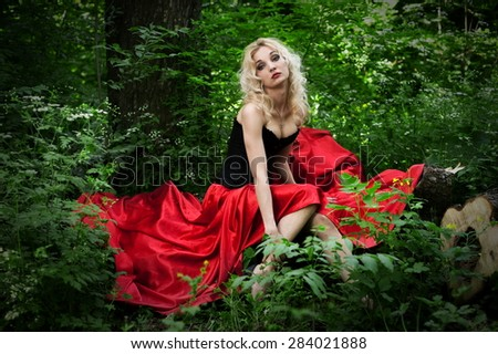 Beautiful sexy blonde in a black corset and red skirt with a train length posing in a forest in the green foliage - stock photo